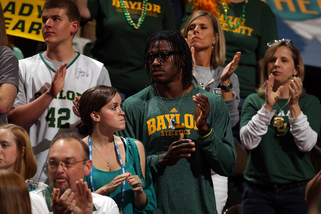 DENVER, CO - APRIL 01:  Heisman trophy winning quarterback Robert Griffin III from the Baylor Bears and his fiancee Rebecca Liddicoat (L) support the Baylor Bears against the Stanford Cardinal during the National Semifinal game of the 2012 NCAA Division I Women's Basketball Championship at Pepsi Center on April 1, 2012 in Denver, Colorado.  (Photo by Doug Pensinger/Getty Images)