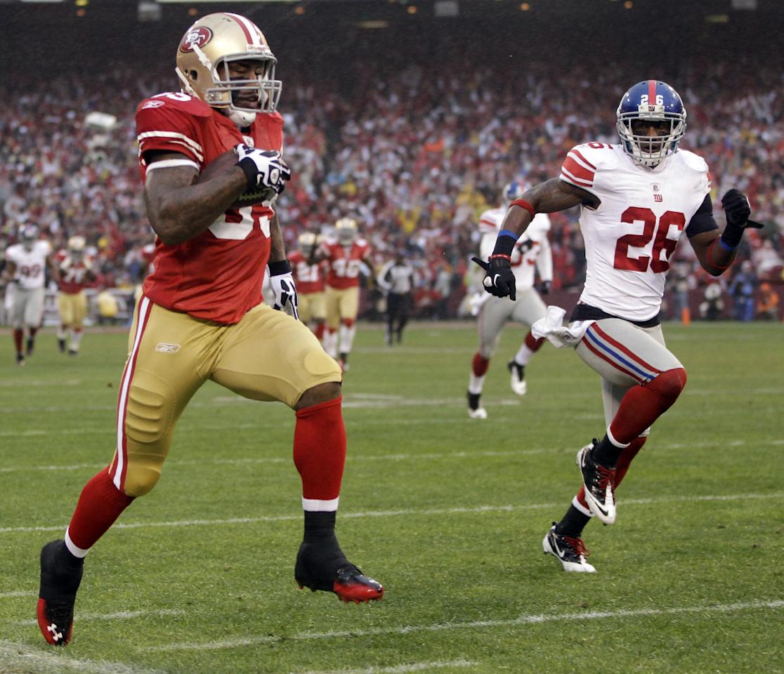 San Francisco 49ers' Vernon Davis (85) stays in bounds as run runs past New York Giants' Antrel Rolle (26) for a 73-yard touchdown reception during the first half of the NFC Championship NFL football game Sunday, Jan. 22, 2012, in San Francisco. (AP Photo/Paul Sakuma)