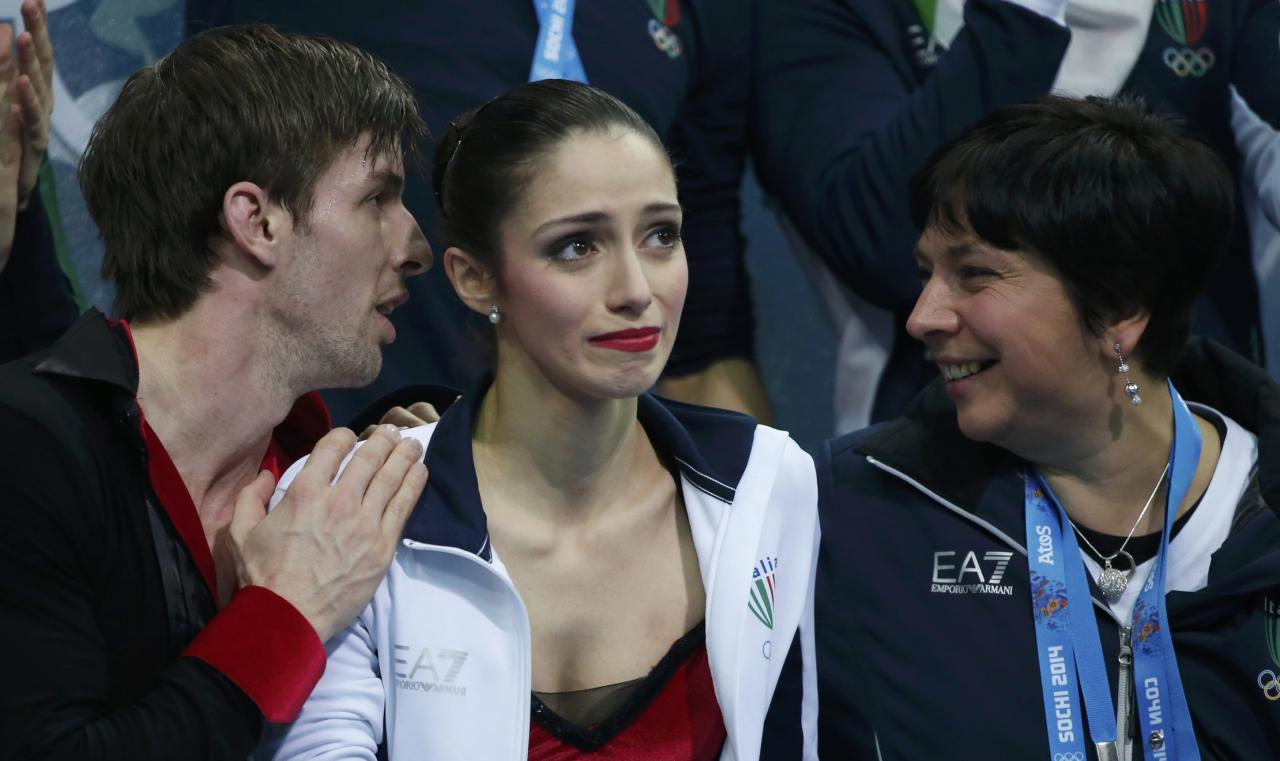 Stefania Berton (C) and Ondrej Hotarek (L) of Italy react at the kiss and cry after their figure skating team pairs free skating at the Sochi 2014 Winter Olympics, February 8, 2014. REUTERS/Lucy Nicholson (RUSSIA - Tags: SPORT OLYMPICS SPORT FIGURE SKATING)