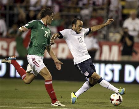 United States' Donovan fights for the ball with Mexico's Mier during the first half of their 2014 World Cup qualifying soccer match in Columbus