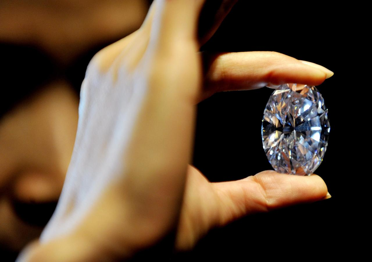 A Sotheby's employee holds the white diamond at 118.28 carats, the largest D colour Flawless diamond, estimated between £18-22 million, during a preview of the auction house's forthcoming London Rocks sale in October, when two diamonds, the white diamond and the worlds largest round fancy vivid blue diamond, a 7.59 Carat stone, estimated in excess of £12 million, are expected to fetch over £30 million between them at the sale.
