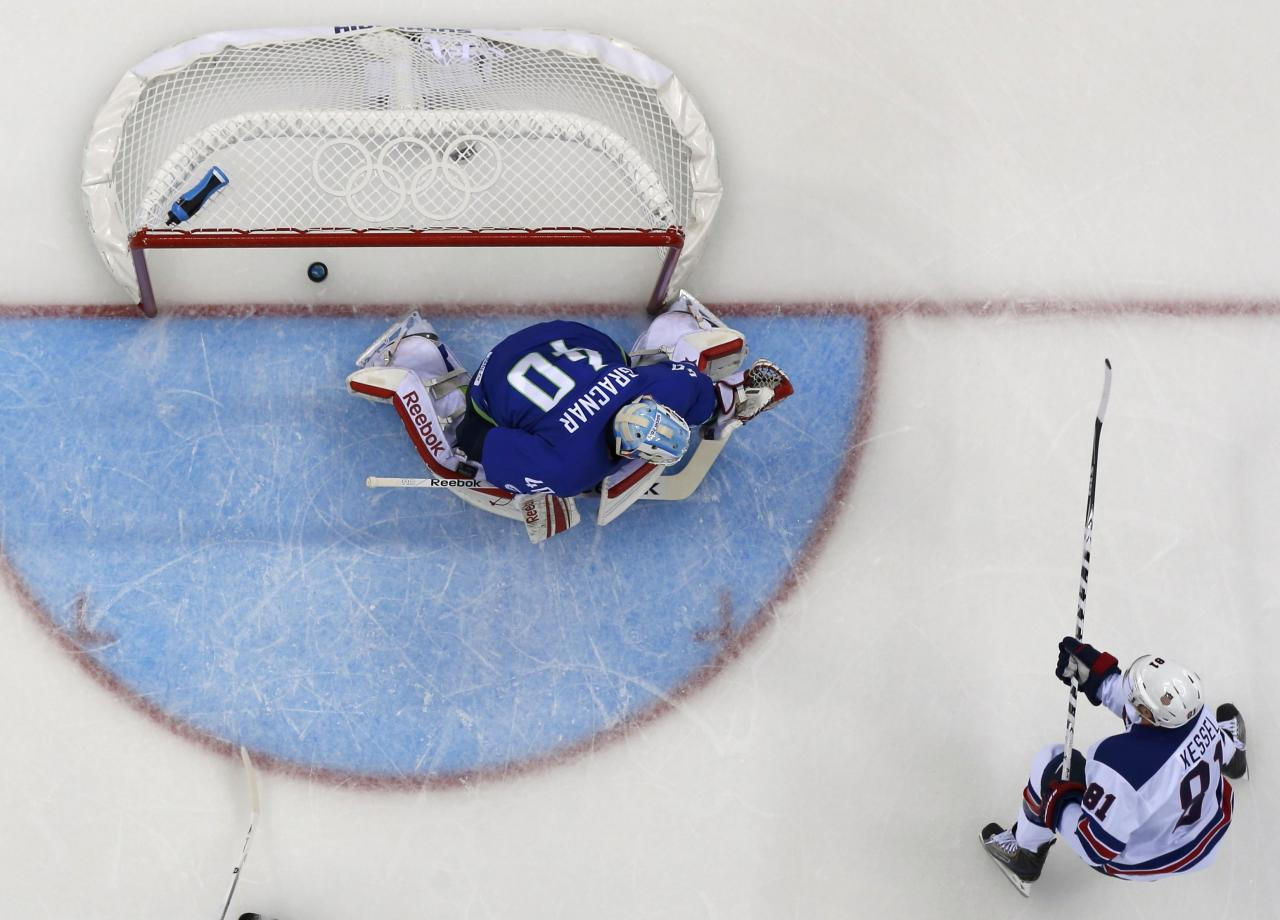 Team USA's Phil Kessel scores a goal on Slovenia's goalie Luka Gracnar during the first period of their men's preliminary round ice hockey game at the 2014 Sochi Winter Olympics, February 16, 2014. REUTERS/Brian Snyder (RUSSIA - Tags: OLYMPICS SPORT ICE HOCKEY TPX IMAGES OF THE DAY)