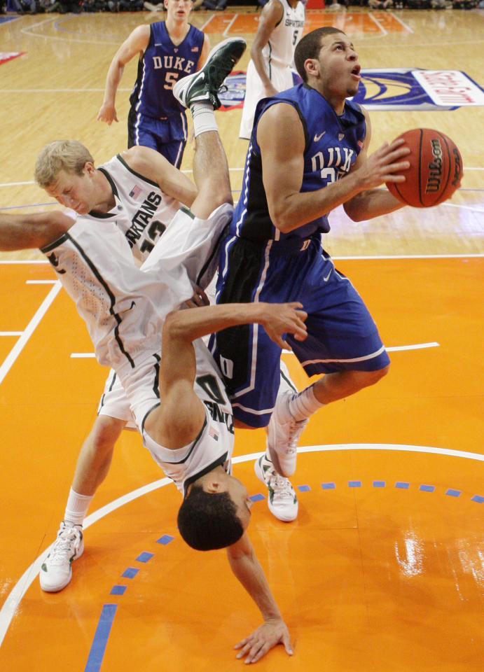 Michigan State's Travis Trice (20) falls over Duke's Seth Curry (30) during the first half of an NCAA college basketball game Tuesday, Nov. 15, 2011, in New York. (AP Photo/Frank Franklin II)