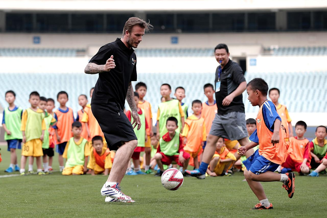 BEIJING, CHINA - JUNE 18: David Beckham plays football with children at Nanjing Olympic Sports Center on June 18, 2013 in Nanjing, Jiangsu Province of China. (Photo by Lintao Zhang/Getty Images)