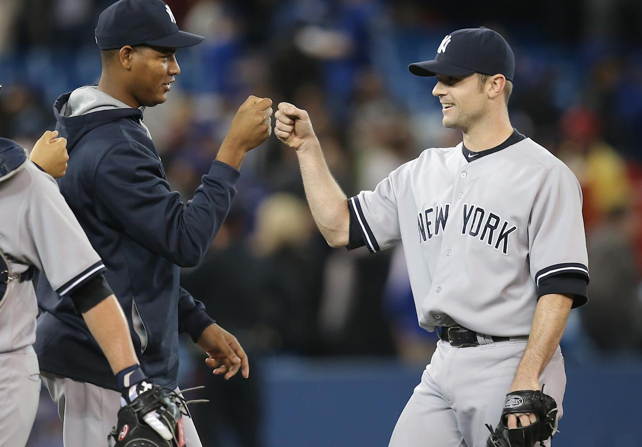 TORONTO, CANADA - APRIL 6: David Robertson #30 of the New York Yankees is congratulated by Ivan Nova #47 during MLB game action against the Toronto Blue Jays on April 6, 2014 at Rogers Centre in Toronto, Ontario, Canada. (Photo by Tom Szczerbowski/Getty Images)