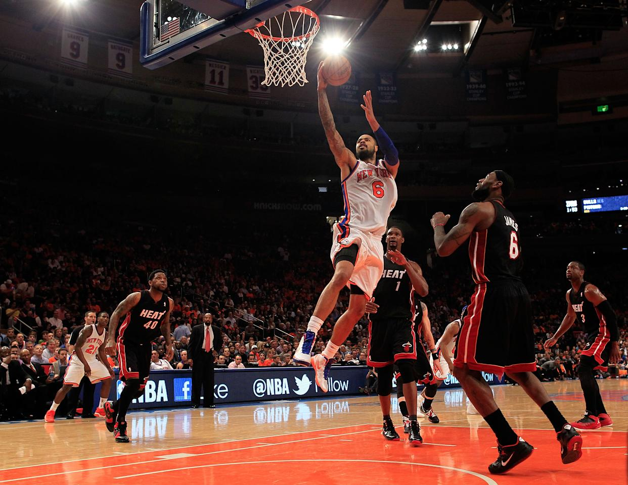 NEW YORK, NY - APRIL 15:  Tyson Chandler #6 of the New York Knicks lays the ball up past LeBron James #6 of the Miami Heat at Madison Square Garden on April 15, 2012 in New York City. NOTE TO USER: User expressly acknowledges and agrees that, by downloading and/or using this Photograph, user is consenting to the terms and conditions of the Getty Images License Agreement.  (Photo by Chris Trotman/Getty Images)