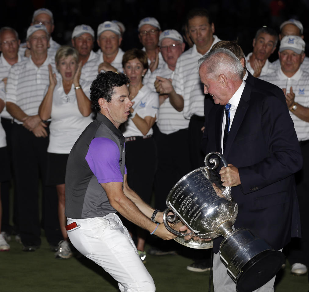 Rory McIlroy, of Northern Ireland, catches the Wanamaker Trophy from PGA of America president Ted Bishop after winning the PGA Championship golf tournament at Valhalla Golf Club on Sunday, Aug. 10, 2014, in Louisville, Ky. (AP Photo/David J. Phillip)