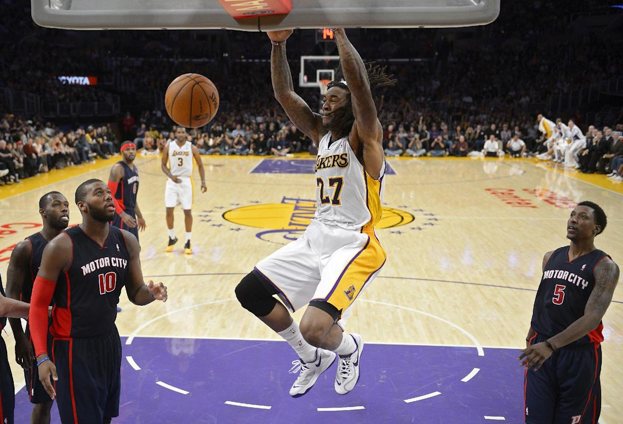 Los Angeles Lakers center Jordan Hill (27) dunks as Detroit Pistons forward Greg Monroe (10) and guard Kentavious Caldwell-Pope (5) look on during the second half of an NBA basketball game, Sunday, Nov. 17, 2013, in Los Angeles. (AP Photo/Mark J. Terrill)