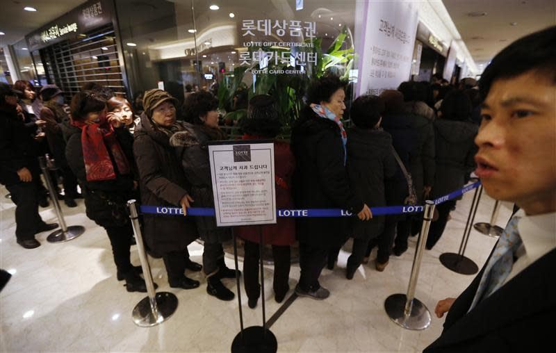 An apology to customers is displayed as customers wait in a line to apply for their credit cards to be reissued at Lotte Card's main office in Seoul