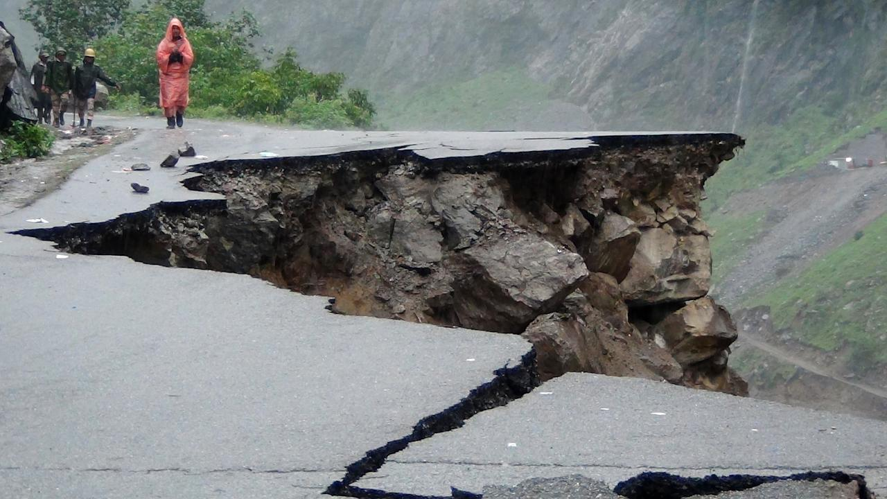 An Indian man looks at damage to a road during heavy monsoon rains near Govindghat town in the Indian state of Uttrakhand on June 17, 2013. Heavy rains lashed parts of north India Monday, resulting in the deaths of at least 18 people, as the annual monsoon covered the country nearly two weeks ahead of schedule, officials said. More than a dozen people lost their lives due to record downpours in Uttarakhand state, situated in the foothills of the Himalayas, a local official said. AFP PHOTO/ STR        (Photo credit should read STRDEL/AFP/Getty Images)