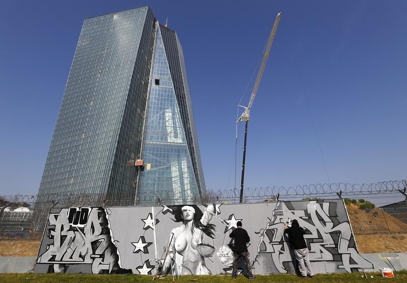 """Artists Justus Becker and """"Bobby Borderline"""" work on their graffiti co-production outside a fence surrounding the construction site for the new head quarters of the European Central Bank in Frankfurt"""