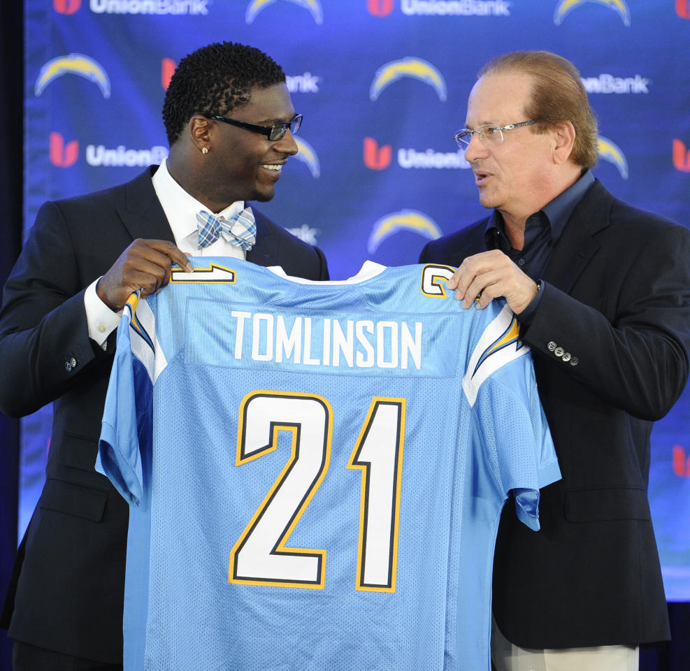 Former San Diego Chargers running back LaDainian Tomlinson, left, and Chargers president Dean Spanos hold up Tomlinson's #21 jersey at a news conference held at the San Diego Chargers facility Monday, June 18, 2012 in San Diego. The news conference was held so that Tomlinson could re-sign with the Chargers and then retire as a Charger. (AP Photo/Denis Poroy)