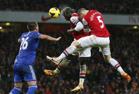 Arsenal's Sagna and Vermaelen jump to head the ball as Chelsea's Terry looks on during their English Premier League soccer match at The Emirates in London