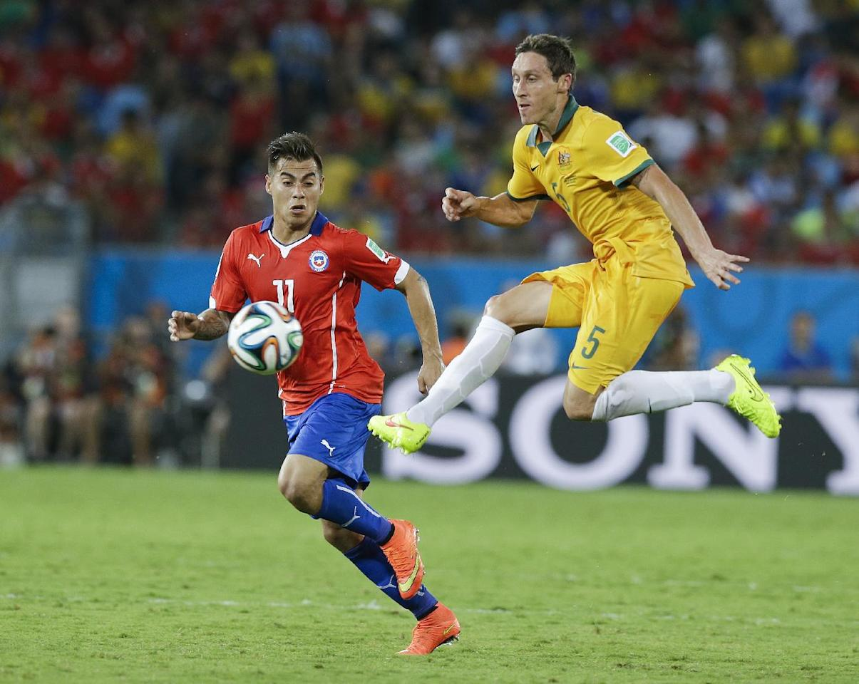 Australia's Mark Milligan (5) kicks the ball past Chile's Eduardo Vargas (11) during the second half of the group B World Cup soccer match between Chile and Australia in the Arena Pantanal in Cuiaba, Brazil, Friday, June 13, 2014. (AP Photo/Thanassis Stavrakis)