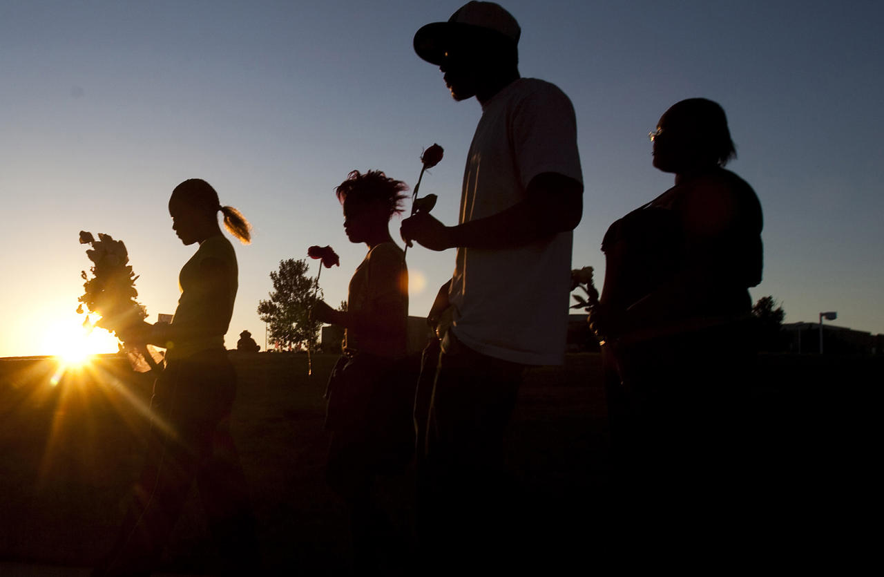 """From left, Tylecia Amos, 14, Shatyra Amos, 15, Michael Walker, 17, and Mykia Walker, 16, carry flowers to lay at a makeshift memorial across the street from the Century Theater parking lot, on Saturday, July 21, 2012 in Aurora, Colo. Twelve people were killed and dozens were injured in the attack early Friday at the packed theater during a showing of the Batman movie, """"Dark Knight Rises."""" Police have identified the suspected shooter as James Holmes, 24. (AP Photo/Barry Gutierrez)"""