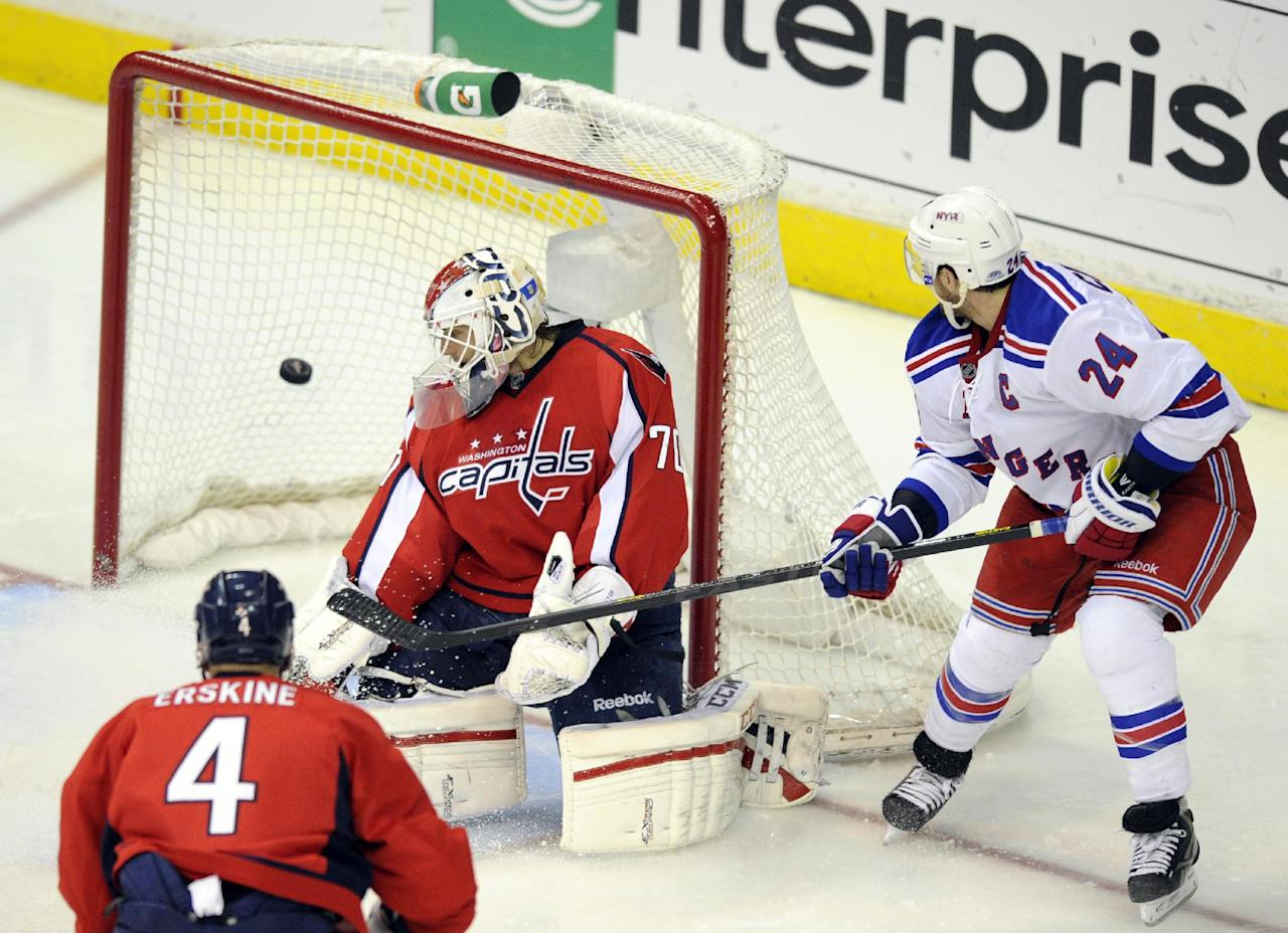 New York Rangers right wing Ryan Callahan (24) scores a goal against Washington Capitals goalie Braden Holtby (70) during the third period of Game 7 first-round NHL Stanley Cup playoff hockey series, Monday, May 13, 2013, in Washington. The Rangers won 5-0. Also seen is Washington Capitals defenseman John Erskine (4). (AP Photo/Nick Wass)