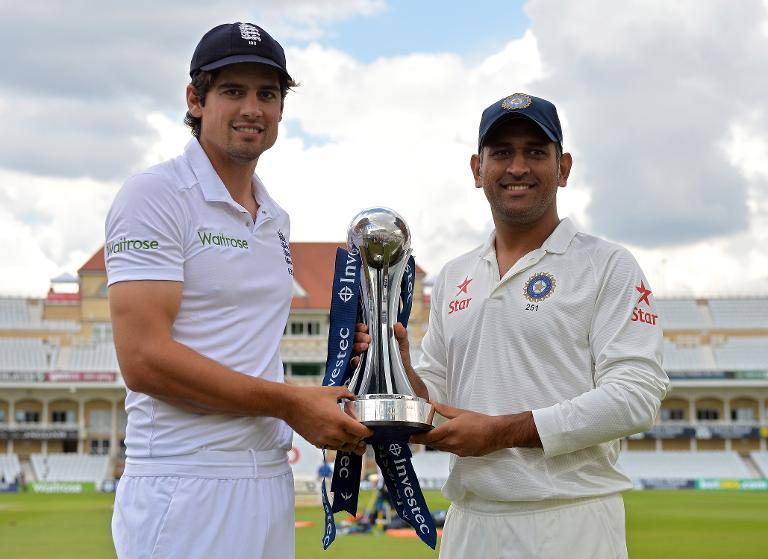 England captain Alastair Cook (left) and Indian captain MS Dhoni pose for pictures with the trophy following team practice sessions at Trent Bridge in Nottingham on July 8, 2014