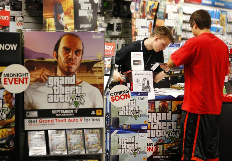 """Game enthusiasts purchase the latest release of """"Grand Theft Auto V"""" after the game went on sale at the Game Stop store in Encinitas, California"""