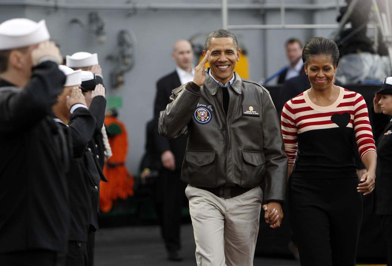 President Barack Obama salutes as he and first lady Michelle Obama walk on the flight deck of the USS Carl Vinson for the Carrier Classic NCAA college basketball game between Michigan State and North Carolina, Friday, Nov. 11, 2011, in Coronado, Calif.(AP Photo/Lenny Ignelzi)