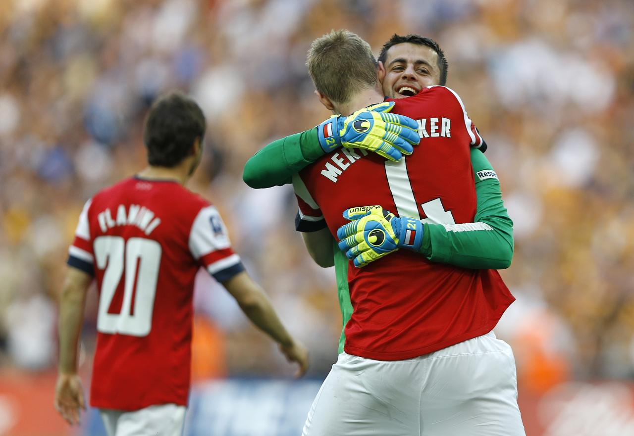 Arsenal's Lukasz Fabianski and Per Mertesacker celebrate after winning the English FA Cup final soccer match between Arsenal and Hull City at Wembley Stadium in London, Saturday, May 17, 2014. Arsenal won 3-2 after extra-time. (AP Photo/Kirsty Wigglesworth)