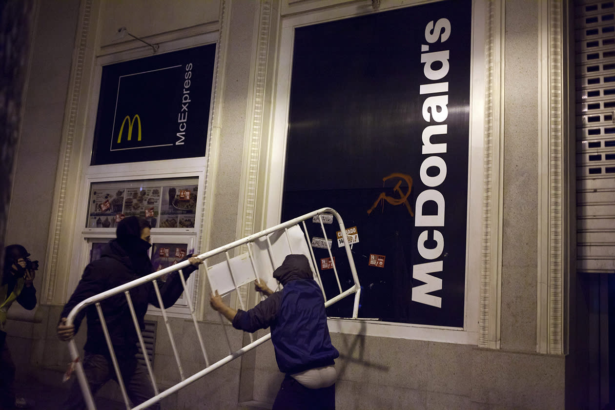 Demonstrators use a fence to break the glass in a McDonald's restaurant during clashes with police following a protest in Madrid.