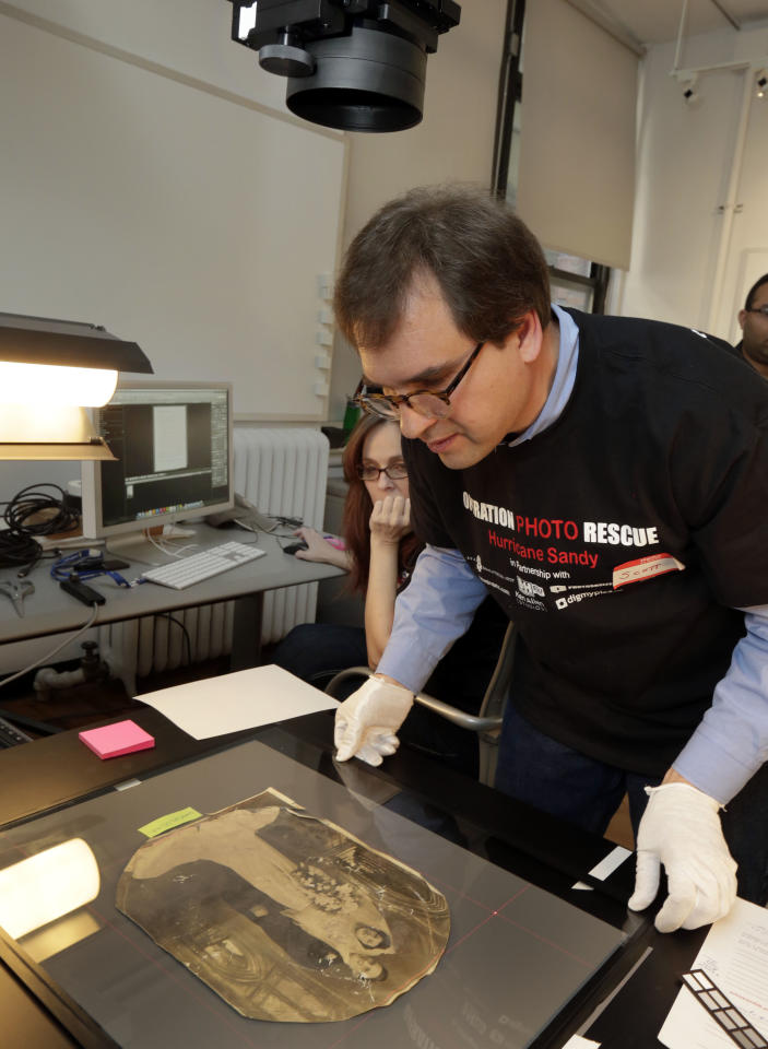 In this Saturday, Feb. 2, 2013 photo, Scott Geffert, senior imaging systems manager of New York's Metropolitan Museum of Art, prepares a damaged photo belonging to Florence Catania, of Deer Park, N.Y., under a high resolution digital copy camera, for restoration by Operation Photo Rescue-Hurricane Sandy, at New York's School of Visual Arts. Of all the pictures of Superstorm Sandy's destruction, some of the most lingering for victims of the storm are the warped, stained ones that sat on the walls and shelves of flooded homes. The Sandy project promises to be one of Operation Photo Rescue's most expert and ambitious efforts yet. (AP Photo/Richard Drew)