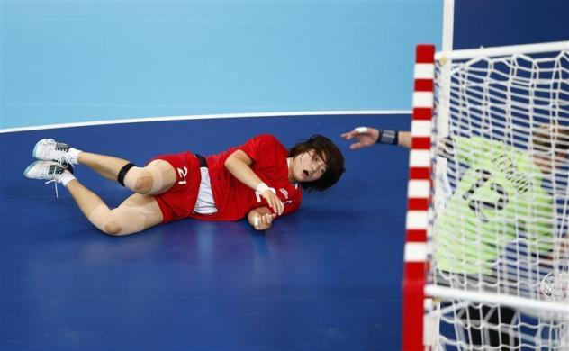 South Korea's Jo Hyobi falls after taking a shot against France in their women's handball Preliminaries Group B match at the Copper Box venue during the London 2012 Olympic Games August 3, 2012.