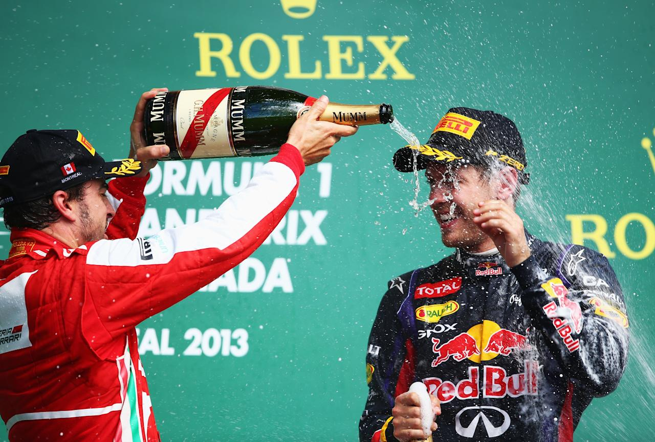 MONTREAL, QC - JUNE 09:  Sebastian Vettel (right) of Germany and Infiniti Red Bull Racing celebrates with second placed Fernando Alonso (left) of Spain and Ferrari following the Canadian Formula One Grand Prix at the Circuit Gilles Villeneuve on June 9, 2013 in Montreal, Canada.  (Photo by Paul Gilham/Getty Images)