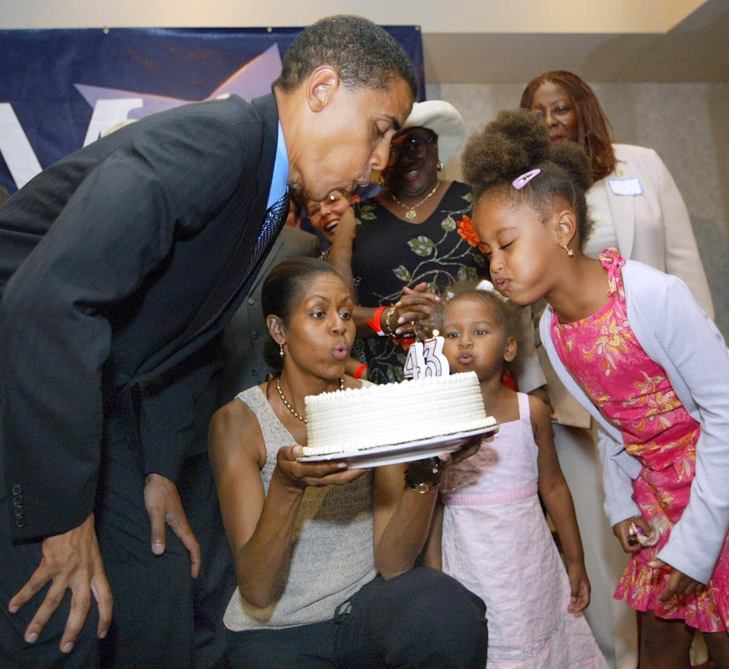 arack Obama blows out candles on his birthday cake at his 43rd birthday celebration with his wife Michelle, who is holding the cake, and daughters Sasha and Malia (R) during a fundraiser August 4, 2004 in Matteson, Illinois. (Photo by Tim Boyle/Getty Images)