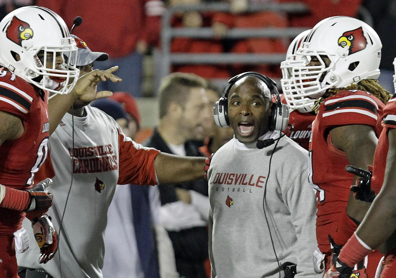 Louisville coach Charlie Strong shouts instructions to his team during a timeout in an NCAA college football game against Houston in Louisville, Ky., Saturday, Nov. 16, 2013. Louisville defeated Houston 20-13. (AP Photo/Garry Jones)