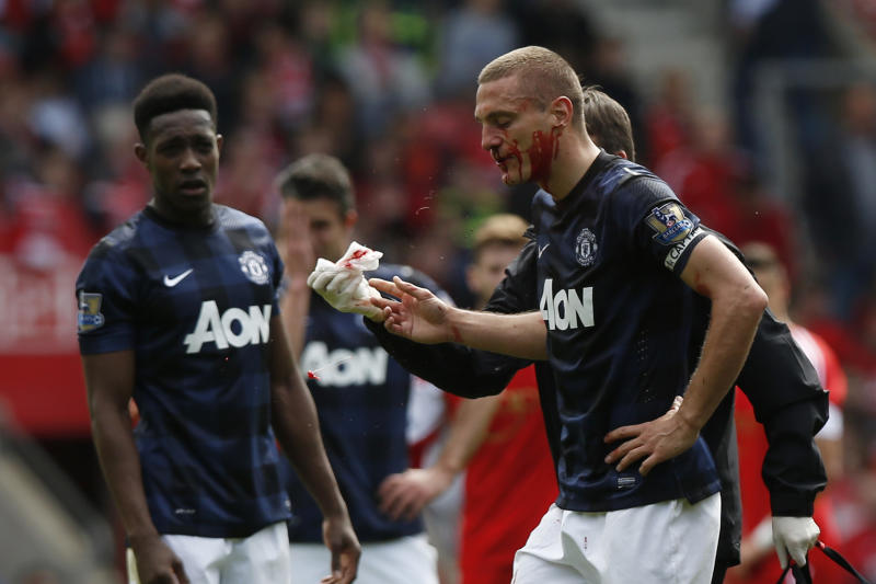 Manchester United's Nemanja Vidic, right, leaves the pitch after a nose bleed during their English Premier League soccer match against Southampton at St Mary's stadium, Southampton, England, Sunday, May 11, 2014