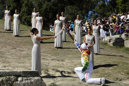 Greek actress Menegaki passes the Olympic flame to Greek skier Antoniou during a dress rehearsal for the torch lighting ceremony of the Sochi 2014 Winter Olympic Games at the site of ancient Olympia in Greece