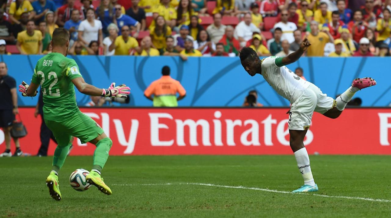 Ghana's Asamoah Gyan, right, scores his side's first goal past Portugal goalkeeper Beto during the group G World Cup soccer match between Portugal and Ghana at the Estadio Nacional in Brasilia, Brazil, Thursday, June 26, 2014. (AP Photo/Paulo Duarte)