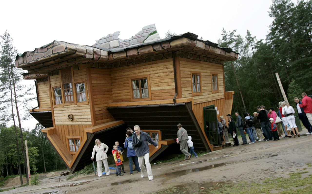 People wait in line to visit an upside-down house built at the Centre of Education and Promotion of the Region in the village of Szymbark, northern Poland July 31, 2007. The upside-down house created by Daniel Czapiewski is supposed to describe the times of the former communist era and the present times in which we live.  REUTERS/Peter Andrews  (POLAND) - RTR1SERQ