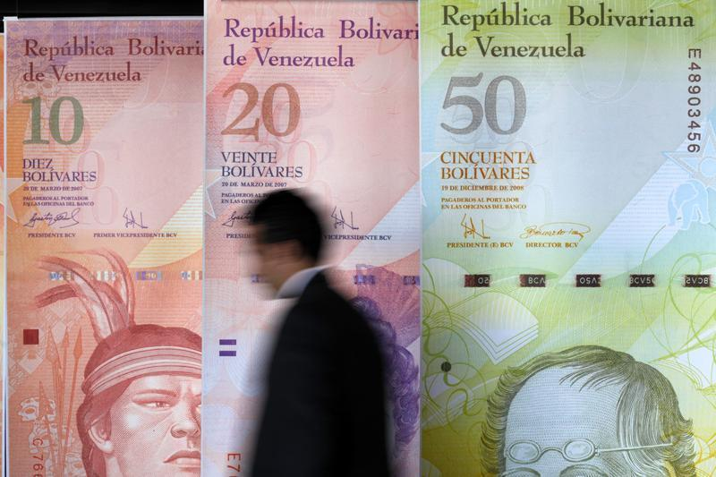 A man walks past big samples of Venezuelan bank notes at the Central Bank headquarters in Caracas