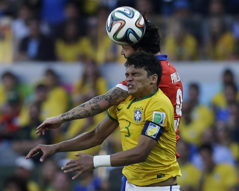 Brazil's Thiago Silva wins a challenge with Chile's Mauricio Pinilla during the World Cup round of 16 soccer match between Brazil and Chile at the Mineirao Stadium in Belo Horizonte, Brazil, Saturday, June 28, 2014