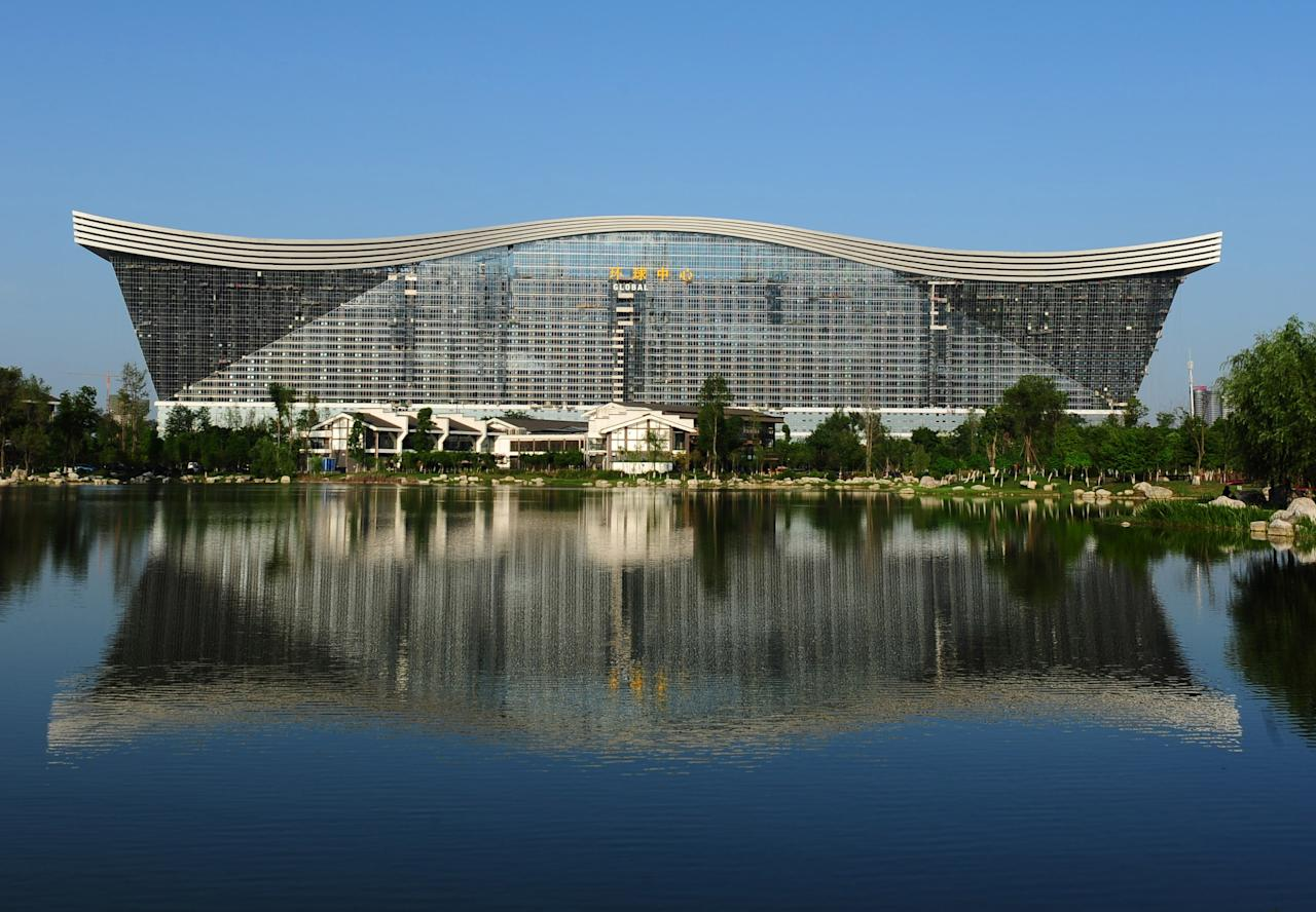 "This picture taken on May 26, 2013 shows the ""New Century Global Centre"" building reflected in an artificial lake in Chengdu, in southwest China's Sichuan province. The center, claimed by Chinese officials as ""the world's largest standalone structure"", is going to be opened to the public on June 28. The 100m high ""New Century Global Centre"" is a symbol of the spread of China's boom: 500m long and 400m wide, with 1.7 million square metres of floor space - big enough to hold 20 Sydney Opera Houses, according to local authorities.  CHINA OUT     AFP PHOTO"