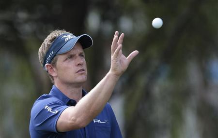 Luke Donald of Britain gets his ball back from his caddy on the fifth hole during the second round of the WGC-HSBC Champions golf tournament in Shanghai