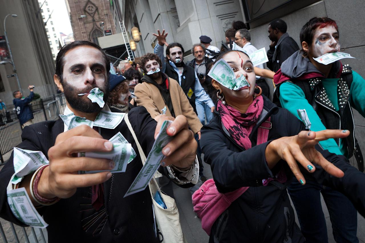 """<p>               Protesters from Occupy Wall Street march through New York's financial district dressed as """"corporate zombies"""" Monday, Oct. 3, 2011. The protests have gathered momentum and gained participants in recent days as news of mass arrests and a coordinated media campaign by the protestors have given rise to similar demonstrations around the country. (AP Photo/John Minchillo)"""