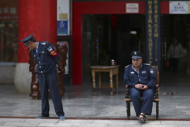 Security guards are seen on duty in front of a jewellery store in Kunming