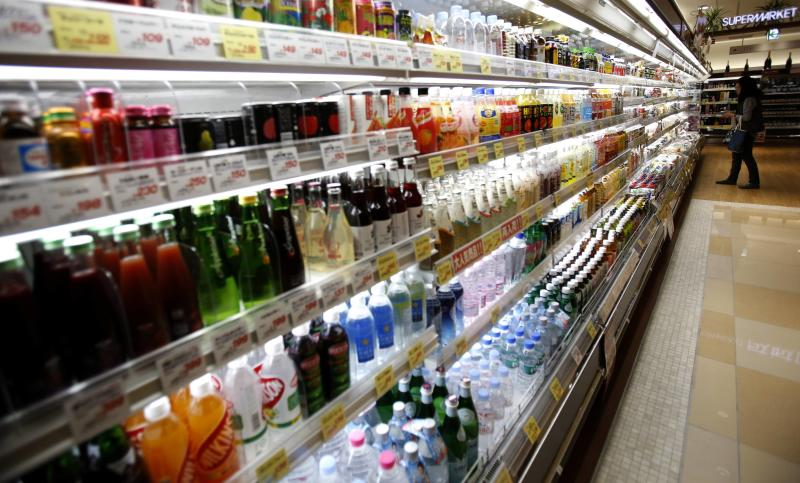 A woman looks at drinks at a supermarket at Ginza shopping district in Tokyo