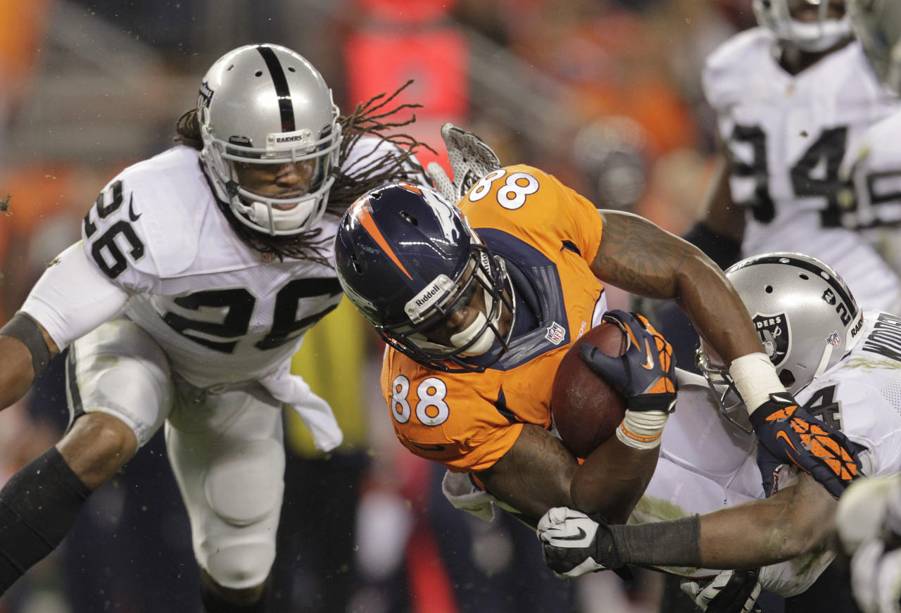 Denver Broncos wide receiver Demaryius Thomas (88) is tackled by Oakland Raiders free safety Charles Woodson (24) and free safety Usama Young (26) in the third quarter of an NFL football game, Monday, Sept. 23, 2013, in Denver. (AP Photo/Joe Mahoney)