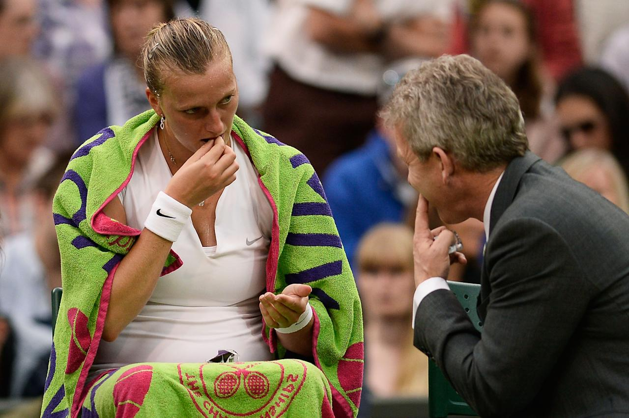 LONDON, ENGLAND - JULY 02: Petra Kvitova of Czech Republic receives treatment during the Ladies' Singles quarter-final match against Kirsten Flipkens of Belgium on day eight of the Wimbledon Lawn Tennis Championships at the All England Lawn Tennis and Croquet Club at Wimbledon on July 2, 2013 in London, England. (Photo by Dennis Grombkowski/Getty Images)