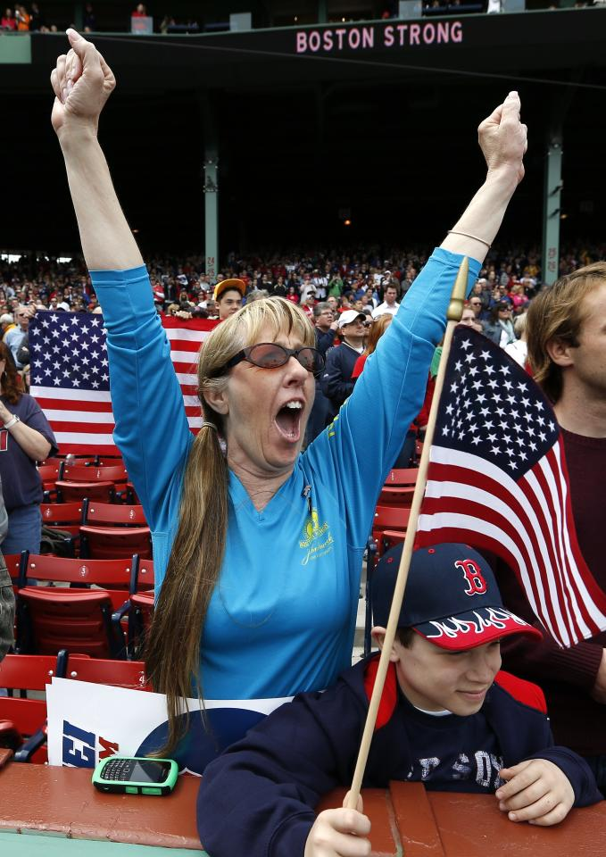 A fan cheers during a tribute to first responders to the Boston Marathon bombing before a baseball game between the Boston Red Sox and the Kansas City Royals in Boston, Saturday, April 20, 2013. (AP Photo/Michael Dwyer)