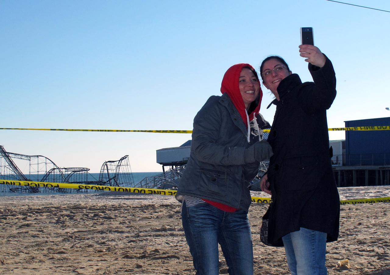 Alisa Brennan, left, and Julia Heffernan, both of Little Egg Harbor Township, N.J., take a photo of themselves on Monday, Jan. 7, 2013, in front of the Jet Star roller coaster, which plunged into the ocean during Superstorm Sandy in Seaside Heights, N.J. Monday was the first day that some of the hardest-hit parts of the Jersey shore allowed residents to move back home. (AP Photo/Wayne Parry)