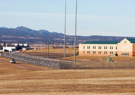 "A patrol vehicle is seen along the fencing at the Federal Correctional Complex, including the Administrative Maximum Penitentiary or ""Supermax"" prison, in Florence, Colorado February 21,2007. REUTERS/Rick Wilking/File Photo"