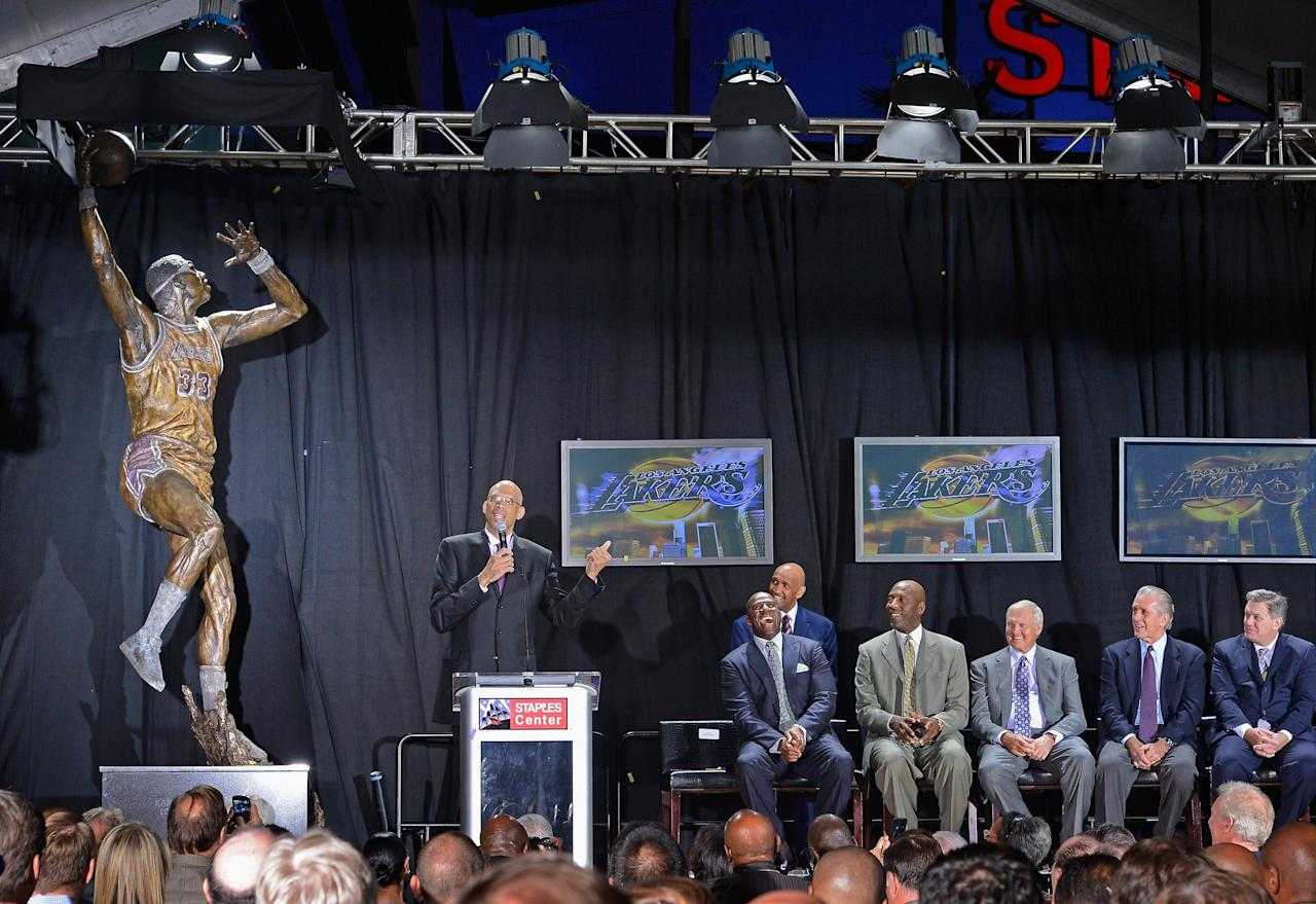 "LOS ANGELES, CA - NOVEMBER 16: Los Angeles Lakers legend Kareem Abdul-Jabbar (L) speaks after unveiling a statue of himself at Staples Center before the Lakers take on the Phoenix Suns on November 16, 2012 in Los Angeles, California. Looking on are as his former teammates Earvin ""Magic"" Johnson (2ndL) James Worthy (3rdL) former Lakers general manager Jerry West, former Lakers coach Pat Riley(2ndR) and AEG president and CEO Tim Leiweke(Photo by Kevork Djansezian/Getty Images)"
