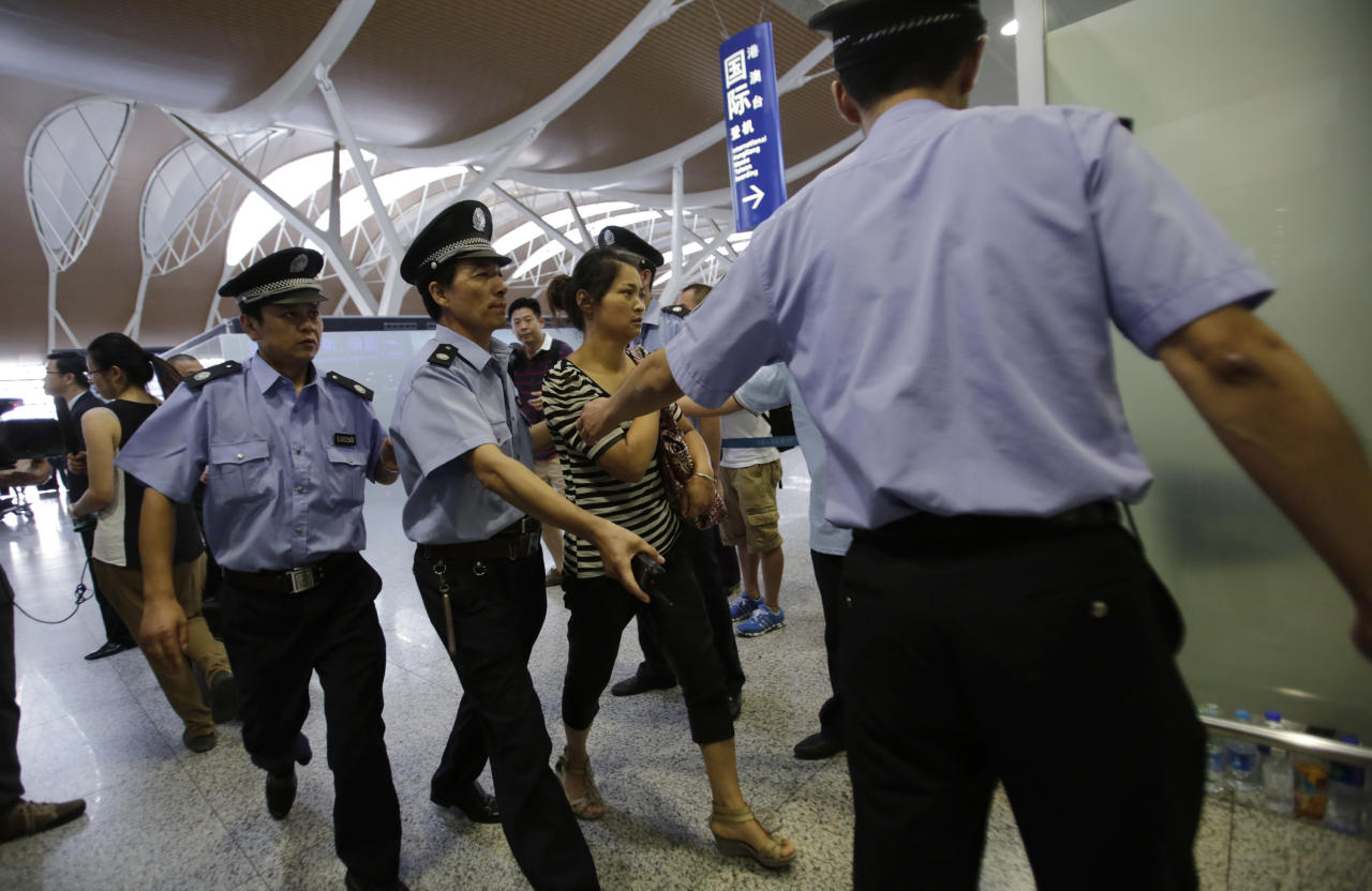 An unidentified family member of one of two Chinese students killed in an Asiana Airlines plane crash on Saturday, is escorted by airport security officers at the Pudong International Airport in Shanghai, China, Monday, July 8, 2013. The Asiana flight crashed upon landing Saturday, July 6, at San Francisco International Airport, and the two of the 307 passengers aboard were killed. (AP Photo/Eugene Hoshiko)