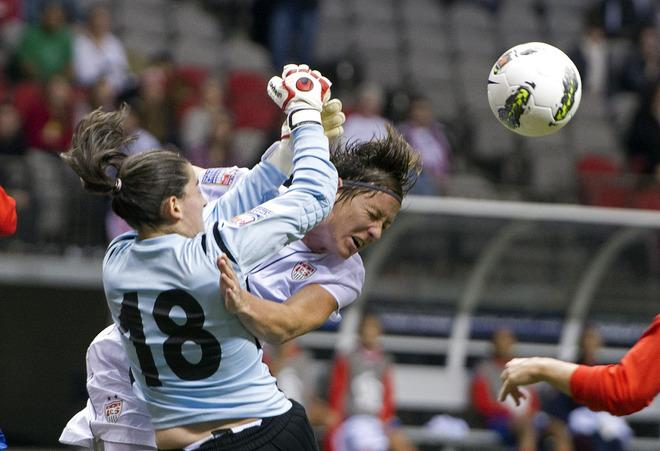 VANCOUVER, CANADA - JANUARY 27:  Abby Wambach #20 of the United States collides with goalie Erika Miranda #18 of Costa Rica while battling for the loose ball during the first half of semifinals action of the 2012 CONCACAF Women's Olympic Qualifying Tournament at BC Place on January 27, 2012 in Vancouver, British Columbia, Canada.  (Photo by Rich Lam/Getty Images)