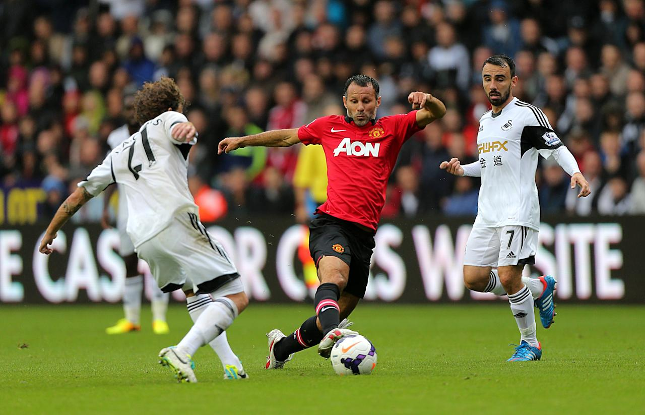 Manchester United's Ryan Giggs (centre) tries to get away from Swansea City's Jose Alberto Canas